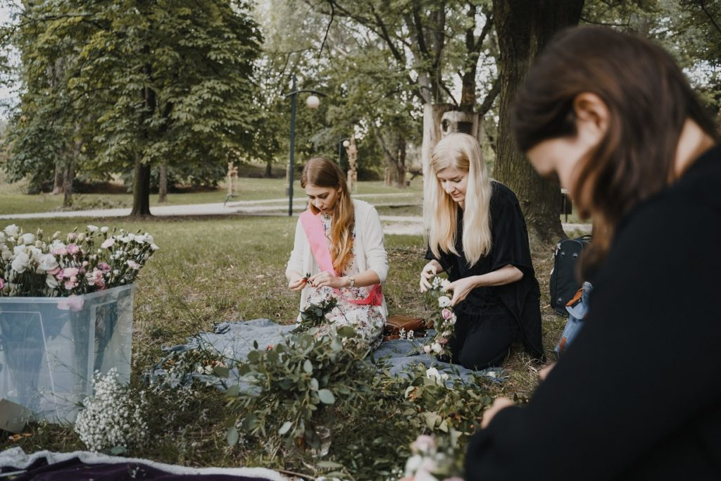 3 osoby wyplatające wianek pełen kwiatów