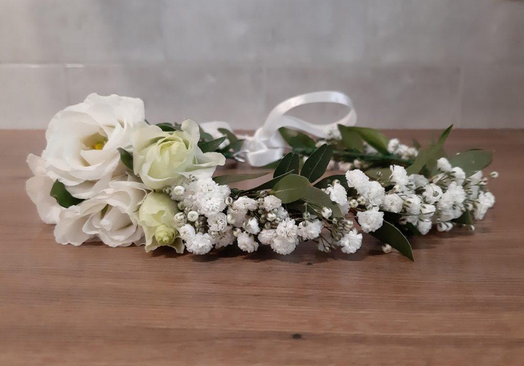 Wianek wykonany z gipsówki oraz kilku kwiatów eustomy umieszczonych asymetrycznie.