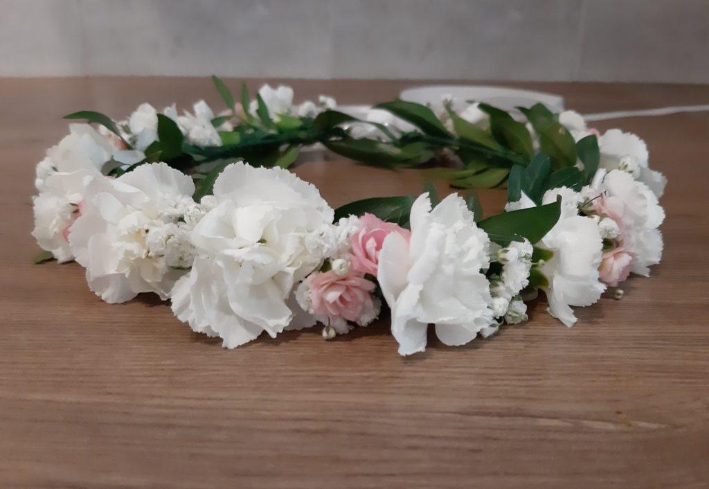 Wianek komunijny z białych goździków z dodatkiem różowych kwiatów.