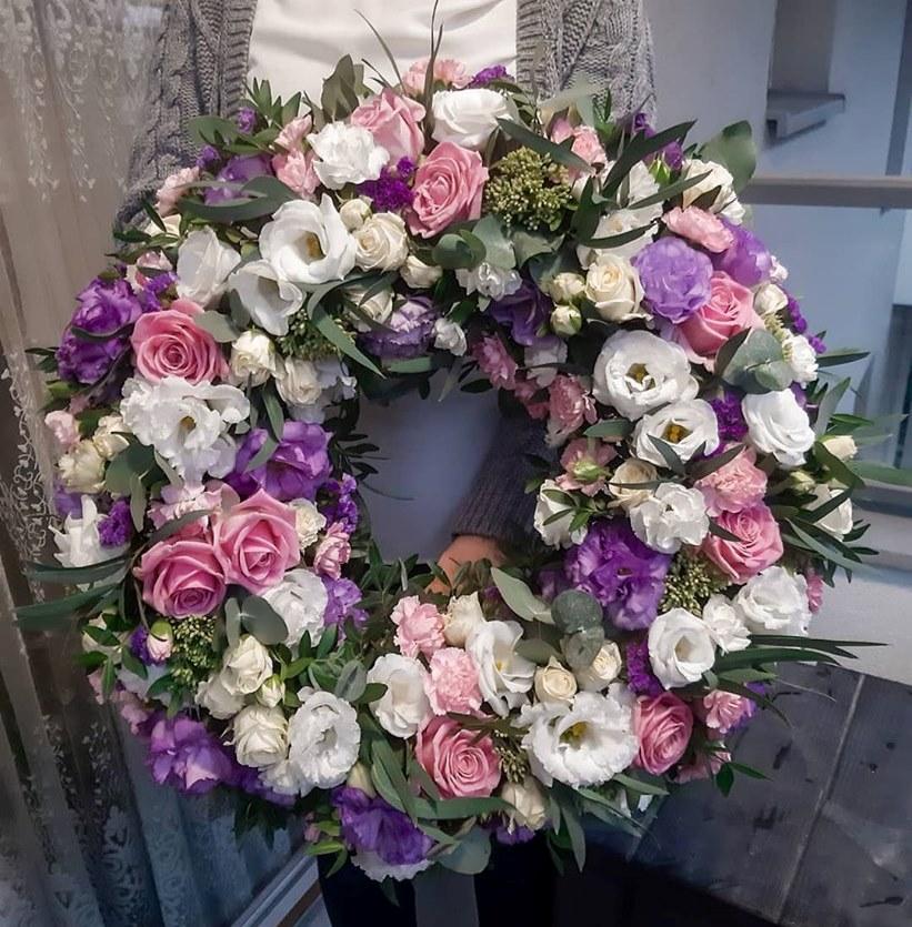 Wieniec pogrzebowy. Kwiaty w kolorystyce bieli, różu oraz fioletu.